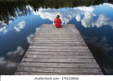 Summertime. Boy dressed in a red jacket sitting on a pier and looking at the lake.