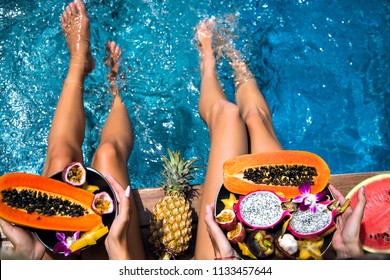 Summertime close up picture of two woman sitting near pool holding big plates with amazing sweet tasty tropical exotic fruits, papaya, mangosteen, dragon fruit watermelon and pineapple, healthy vegan.