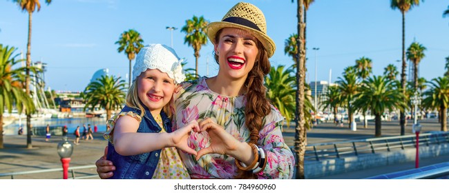 Summertime at colorful Barcelona. happy elegant mother and daughter tourists in Barcelona, Spain showing heart shaped hands