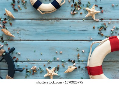 Summertime concept with lifeboats, rudder, seashells, starfishes and marine rubble on a blue wooden background. Top view. Copy space.