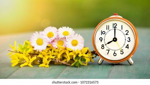 Summertime concept - web banner of fresh flowers and orange retro alarm clock