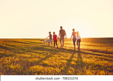 Summertime in the countryside. Silhouettes of the family with dog on the trip at the sunset.