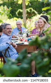 Summertime. a family of three generations gathered around a table in the garden,  to share a meal. Handsome couple looking at camera