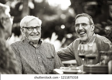 Summertime, a family with three generations gathered around a table in the garden to share a meal. Closeup on a son having fun with his old dad. black and white