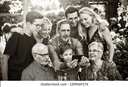 Summertime, a family with three generations having fun around a table in the garden sharing a meal. The whole guest having fun watching a video on a phone. black and white