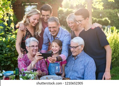 Summertime, a family with three generations having fun around a table in the garden sharing a meal. The whole guest having fun watching a video on a phone