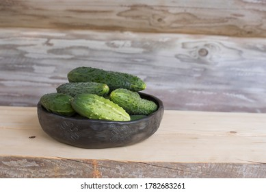 Summertime with fresh green cucumbers in unique handmade ceramic bowl decorated with Baltic folk signs