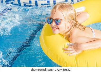 Summertime fun. Pretty little girl swimming in outdoor pool