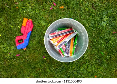 Summertime fun represented by a bucket full of popsicles and a water gun on the grass