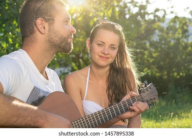 Summertime in garden. Young couple is playing acoustic guitar in the garden at sunset.