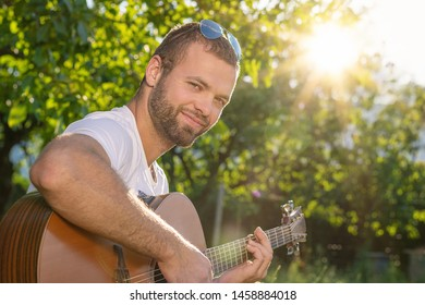 Summertime in garden. Young man is playing acoustic guitar in the garden at sunset.