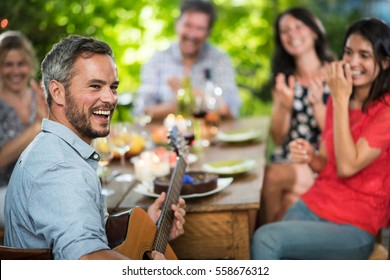 Summertime. Handsome gray haired man enjoying playing guitar for his friends. They gathered around a terrace table where they shared a meal
