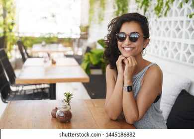 Summertime happiness concept. Cheerful happy tanned young female tourist enjoying summer vacation tropical island trip sit hotel outdoor cafe patio wear sunglasses waiting coffee smiling relaxed