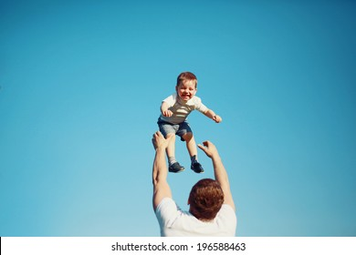 Summertime! Happy joyful child, father fun throws up son in the air, carefree, blue sky, family, travel, vacation, childhood, father's day - concept. Sunlight on the sunset