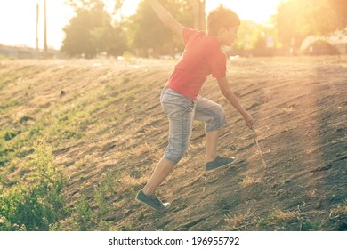 Summertime happyness image of boy climb up slope backlit.