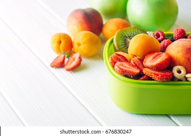 Summertime healthy food concept: Close up of lunch box filled with of fruits, berries and crunches on white wooden background with blank space for text; selective focus