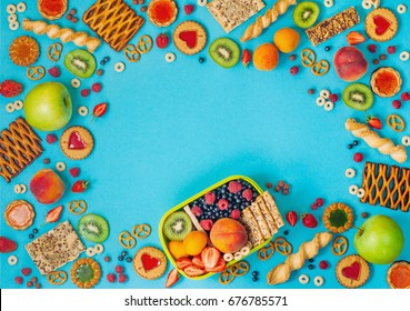 Summertime healthy food concept: Frame with lunch box and mixed of fruits, berries, cookies and crunches around it on blue background with blank space for text; top view, flat lay