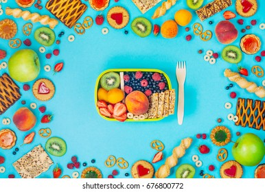 Summertime healthy food concept: Frame with lunch box and mixed of fruits, berries, cookies and crunches on blue background; top view, flat lay