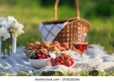 Summertime healthy picnic on nature background at sunny day. Close up Basket fruits strawberries, cherries, glass of red wine, on green grass in garden. Summer weekend outdoor. Beautiful still life