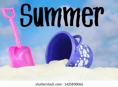 Summertime image of a beach scene on sand with a blue sky that has puffy white clouds in the distance. Pink and purple beach toys are buried in the sand. Text added.