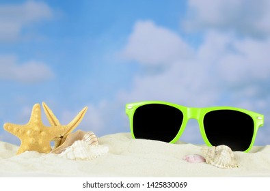 Summertime image of a beach scene on sand with a blue sky that has puffy white clouds in the distance. Fun green sunglasses are buried in the sand among starfish and seashells. Copy space