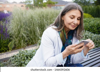 Summertime image of gray haired beautiful retired female sitting on bench with portable electronic gadget, chatting online via messenger. Smiling elegant mature woman using smart phone outdoors
