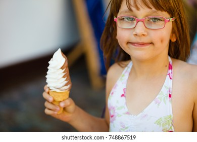 Summertime joy, summer recreation outside concept. Toddler girl in eyeglasses eating ice cream, having fun