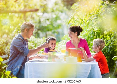Summertime, nice family, Daddy, Mom and their two kids sitting at a table, eating lunch in the garden enjoying a sunny day