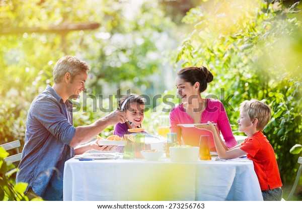Sommerzeit, nette Familie, Daddy, Mutter und ihre beiden Kinder sitzen am Tisch und essen im Garten zu Mittag und genießen einen sonnigen Tag