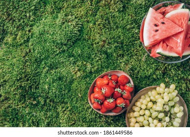Summertime picnic with healthy food - fruits, watermelon, grapes, strawberries on green grass. Top view. Copy space. Romantic date, girl party. Vegan and vegetarian diet.