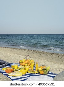 Summertime. A picnic on the beach. Burgers and pitas, vegetables and fruits. Selective focus.
