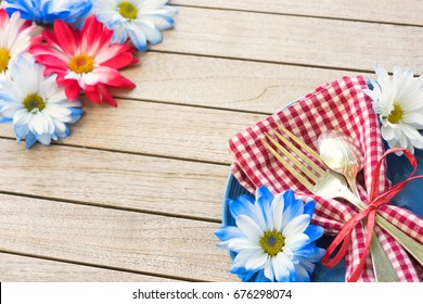 Summertime Picnic Table Place setting with Red White and Blue Flowers, Plate, Napkin, Fork and Spoon on Rustic Wood Board Background with Blank room or space in center for copy, text, or your words.