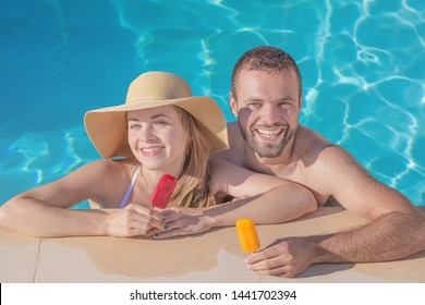 Summertime in pool. Young beautiful couple with ice-cream in swimming pool.