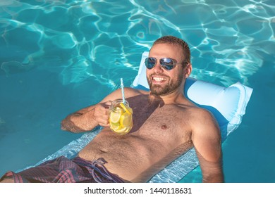 Summertime in pool. Young man floating on inflatable mattress in pool with lemon cocktail.