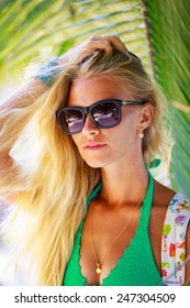 Summertime portrait of beautiful young blonde woman in a green bikini and sunglasses on a tropical background