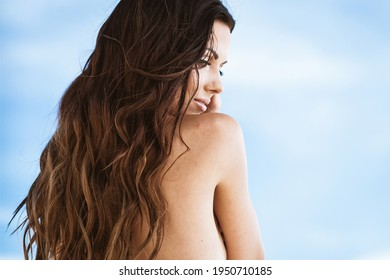 Summertime recreation concept. Beautiful young sexy woman with closeup portrait on a beach. Fashion female model face near the sea