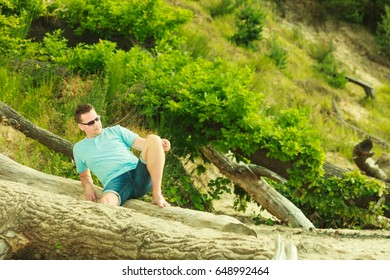 Summertime relaxation, vacation and holiday, adventure traveling concept. Handsome man sitting on tree trunk relaxing during summer.