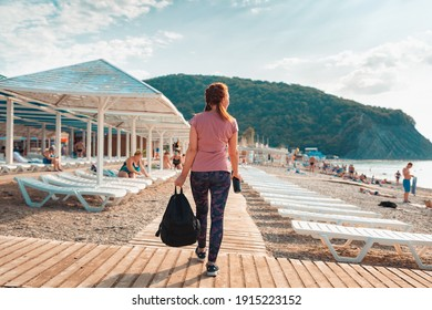 Summertime and resort. A woman in sportswear is walking with a backpack in her hands. Rear view. Copy space. Deckchair and landscape in the background.