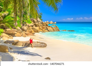 Summertime in Seychelles. Attractive female in red dress sunbathes on boulder in Anse Georgette, a pristine beach of Praslin. Carefree lifestyle woman on paradise beach. Palm trees and turquoise sea.
