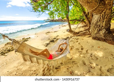 Summertime in Seychelles, Felicite Island. Carefree lifestyle woman on paradise sea. Relaxed woman swinging on the beach in a hammock tropical tree. Blonde girl sleeping in a hammock in luxury resort.