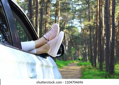 Summertime, summer fun, enjoying, relaxing in the forest, lazy  Sunday, tourism, travel, leisure time, vacation mode, happiness, forest road concept. Young woman's legs out of the car window.