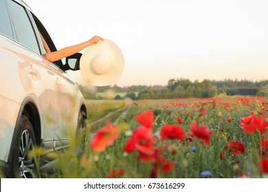 Summertime, summer fun, enjoying, relaxing, tourism, travel, leisure time, vacation mode, happiness concept. Woman enjoying summer vacation. Hands holding white hat out of car window. Selective focus.