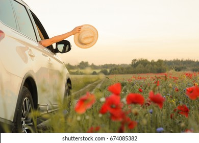 Summertime, summer fun, enjoying, relaxing, tourism, travel, leisure time, vacation mode, happiness concept. Woman enjoying summer vacation. Hands holding hat out of  car window.  Selective focus.