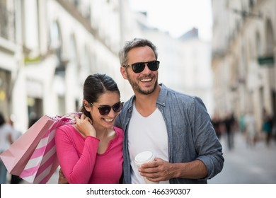 Summertime. A trendy couple walking on the streets, the grey haired man holding a mug of coffee and the brunette woman has shopping bags on her shoulder. they wear sunglasses