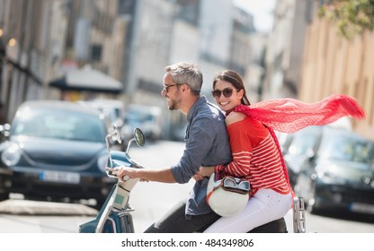 Summertime, a trendy young couple having fun on a vintage scooter in the streets, the man has the gray hair, and the brunette woman has her red scarf flying in the wind