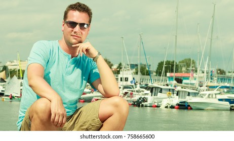 Summertime vacation adventure concept. Man spending his free time walking on marina, sightseeing during summer.