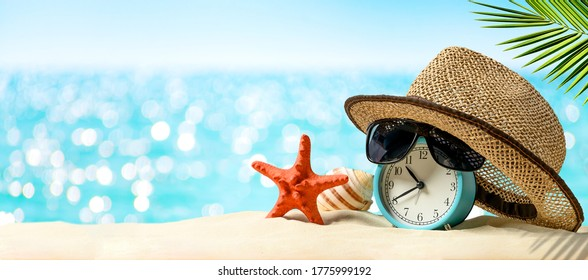Summertime vacation concept. Time to relax. Last minute deals. Alarm clock with straw hat, starfish on the sand beach and sea background.