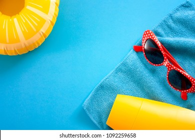 Summertime vacation, day at the beach and summer fun concept with minimalistic top view of polka dot sunglasses, bottle of sun lotion, towel and inflatable ring pool float or lifebuoy on bright blue