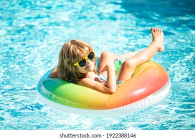 Summertime vacation. Summer kids weekend. Funny boy in swiming pool on inflatable rubber circle at aquapark