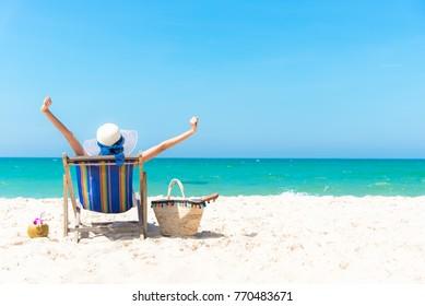 Vacaciones de verano. Hermosa joven asiática relajante y feliz tumbona al aire libre con zumo de coco de cóctel en verano, fondo azul cielo.  Concepto de viajes y estilo de vida
